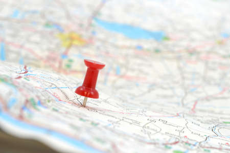 A traveler has used a red pushpin to position the mapped out destination, shallow dof with the focus on the red tack.