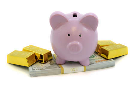 A piggy bank gives security to the savings of gold bullion bars and stack of cash bills.