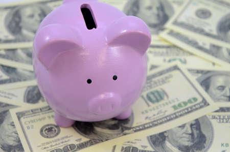 A closeup of a piggy bank overtop of an abundance of American money.