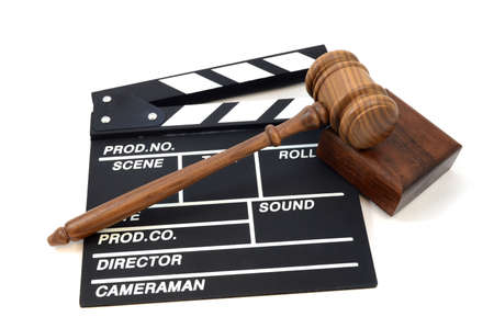 An isolated shot of a movie production clapboard and judges gavel for illustration of industry laws and order. Stock Photo