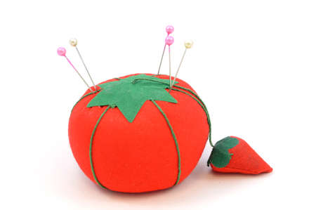 An isolated image of a tomatoe shaped pin cushion for holding pins while doing needle work. Stock Photo