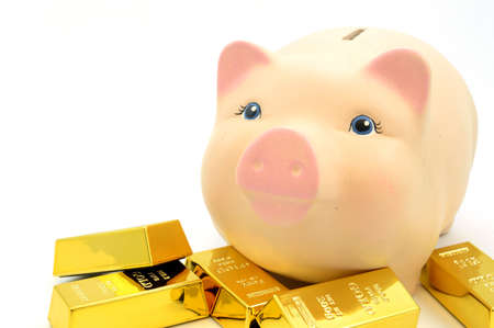 Closeup view of several gold bullion bars next to a piggy bank. Banco de Imagens