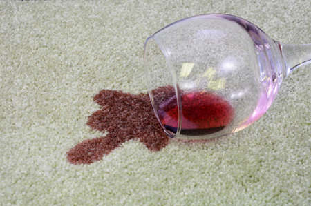 A glass of red wine has been spilled onto a white carpet.