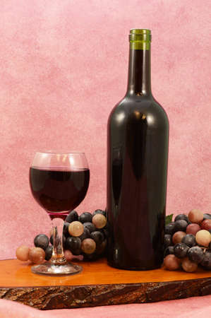 A fresh bottle of red wine just opened and served with a single glass.