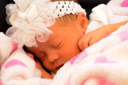 Closeup of a softly filtered focused new born baby girl who is gently drifted away in a sleepy cuteness.