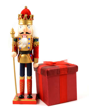 An isolated over white image of a king nutcracker with a red Christmas gift.