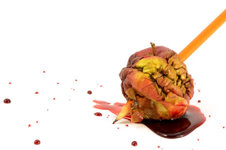 A closeup view of one bad apple being stabbed by a pencil with blood spilling.