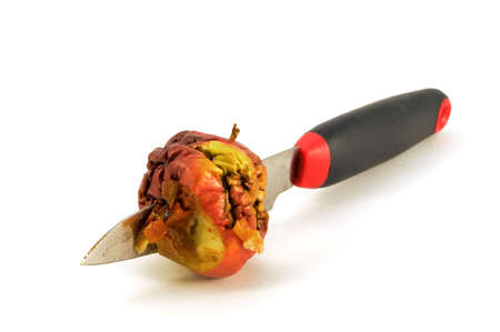 An isolated shot of one bad apple being cut by a knife. 版權商用圖片