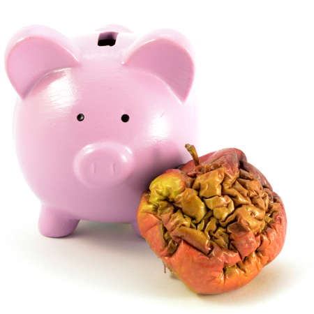 A conceptual image focusing on a pig bank and rotten apple for several monetary ideas. 版權商用圖片