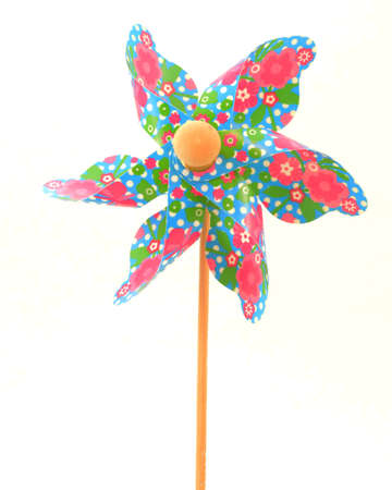 A closeup view of a colorful pin wheel over a white background.