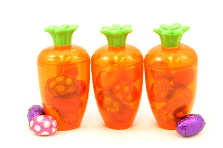 Some festive ways to store Easter candy inside a cute carrot container isolated over white.