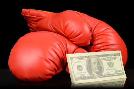 A pair of red boxing gloves with a stack of cash to place a gambling bet.