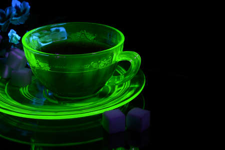 A glowing Uranium Glass Teacup and Saucer under some ultraviolet light to show its unique properties.