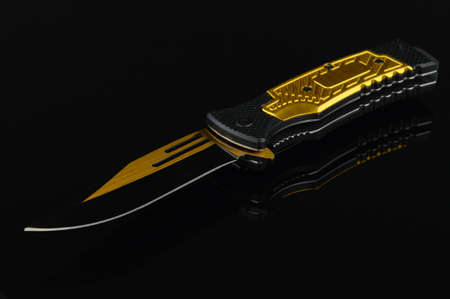 A black and gold pocket knife over a reflective surface.