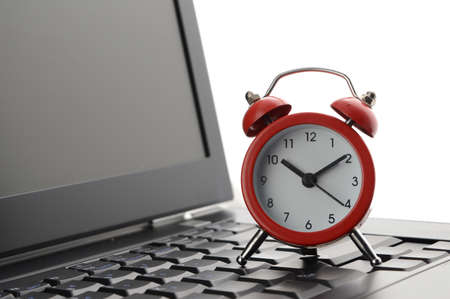 A closeup composition of a laptop and a red alarm clock to conceptualize on business deadlines. Imagens