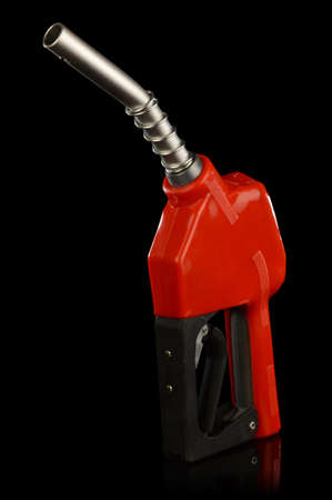 An isolated over a black reflective background image of a modern day red gas pump nozzle.