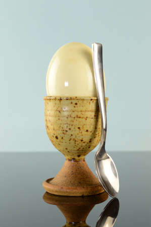 A closeup of a hard boiled egg and spoon to indulge in the breakfast delight. Stock Photo