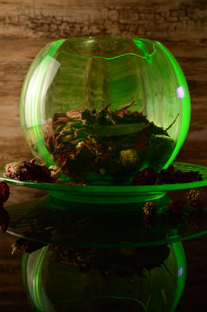 A uranium depression glass rose bowl under an ultraviolet light to reflect its bright green glow that is filled with aromatic potpourri flower mixture.