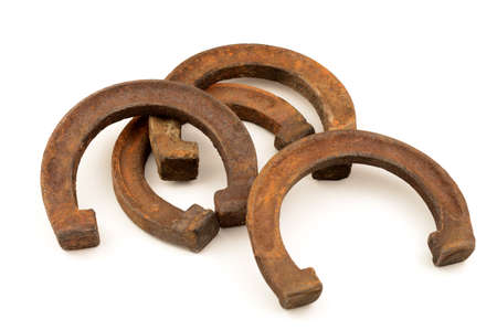 An isolated set of four rustic horse shoes that have been rusted from being weathered.