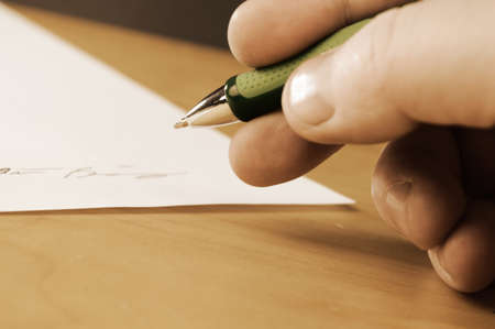 A vintage filter over an image of an important document is being signed by the appropriate person with a closeup of their hand and focus on the tip of the ball point pen.