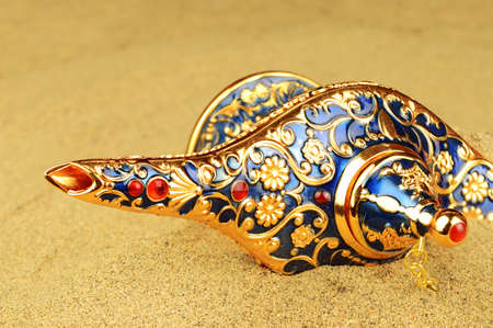 A legendary discovery of a magical Genie lamp shown slightly revealed in the sands over time.