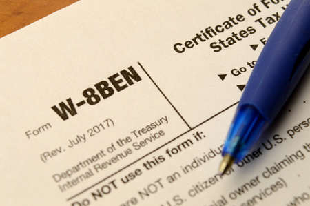 A macro shot of a blank W-8BEN form to fill out for selling copyrighted material in the USA and reduce any taxes held.