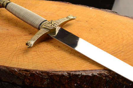 A closeup view of a dagger on a piece of freshly cut wood.