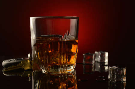 A concept image of drinking and driving utilizing a set of car keys next to a glass of whiskey over a dark reflective black and red background.