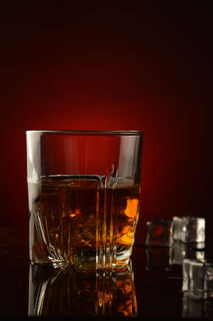 A closeup of a glass full of whiskey and ice over a dark red background with a shallow depth of field on the glass.