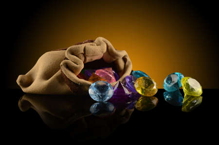 A spilling pouch of gemstones over a dark gradient background.