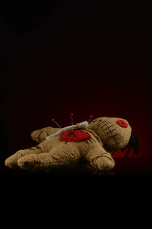 A few pins are stuck inside the heart of a voodoo doll over a dark red and black background.