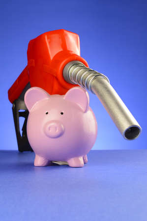 A concept of saving money at the gas pumps using a piggy bank and red fuel pump over a blue background.