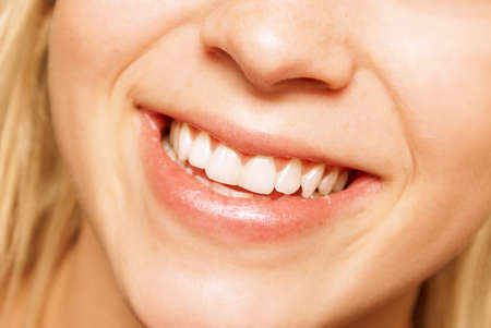 A young woman smiles happily at the viewer in this closeup image.