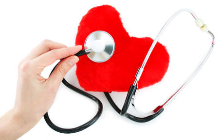 corazon: Hand with stethoscope checking a red heart isolated on a white background