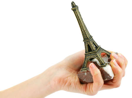 Womans hand holding statuette of Eiffel Tower isolated on a white background photo
