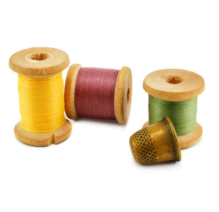 Spools of thread and thimble isolated on a white background photo