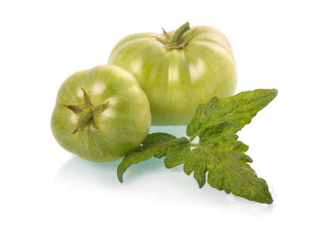 Green tomatoes vegetables with leaves isolated on white background