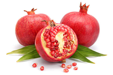 Pomegranate fruits with green leaf and cuts isolated on white background