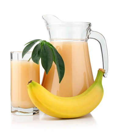 Full glass and jug of banana juice and fruits isolated on white background