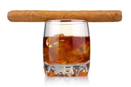 Glass of whiskey with ice cubes and havana cigar isolated on white background photo