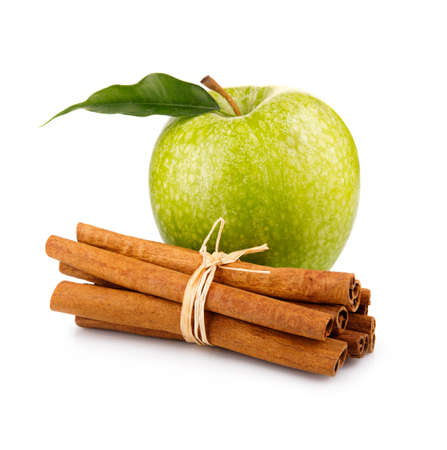 Ripe green apple with cinnamon sticks isolated on white background
