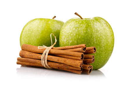 Ripe green apples with cinnamon sticks isolated on white background