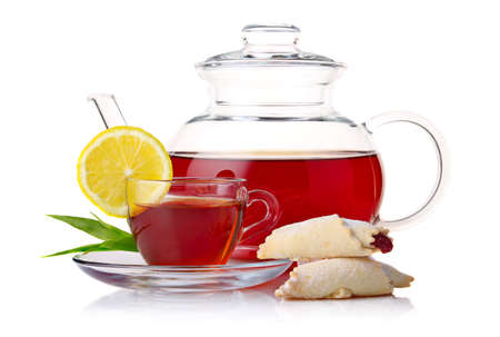 Teapot and cup of black tea with crescent and lemon slice isolated on white background photo