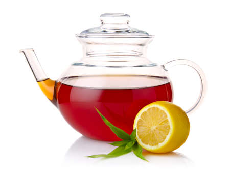 Teapot with black tea, green leaves and lemon slices isolated on white background photo
