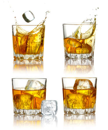 Set of scotch whiskey glasses with splash and ice isolated on a white Stock Photo