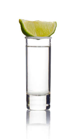 Tequila shot with lime slice isolated on white background