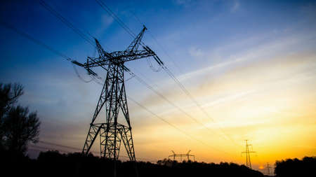 High-voltage transmission power towers silhouette in sunset background Stock Photo