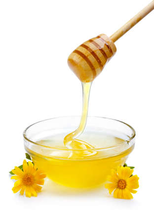 Sweet honey pouring from wooden dipper in glass bowl isolated on white