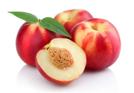 Three ripe peach (nectarine) fruits with slices isolated on white Standard-Bild