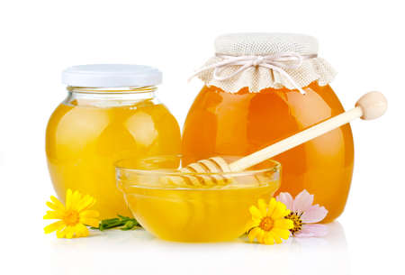 Sweet honey in glass jars with flowers and dipper isolated on white background  photo
